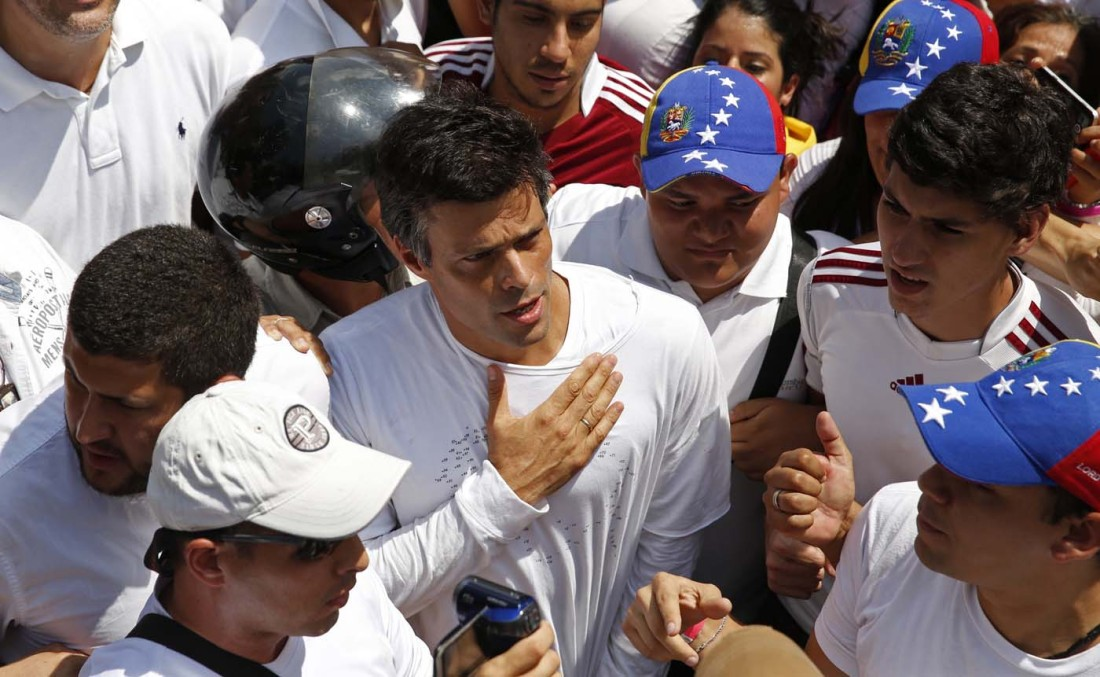 Venezuela's opposition leader Leopoldo Lopez (C), wanted on charges of fomenting deadly violence, walks through a demonstration of his supporters opposed to the government of Nicolas Maduro in Caracas February 18, 2014. Lopez, a 42-year-old U.S.-educated economist who has spearheaded a recent wave of protests in Venezuela, handed himself over to security forces on Tuesday, Reuters witnesses said.  REUTERS/Carlos Garcia Rawlins (VENEZUELA - Tags: POLITICS CIVIL UNREST CRIME LAW TPX IMAGES OF THE DAY)