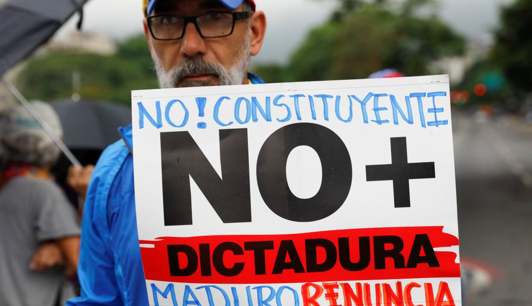"""An opposition supporter holds a placard that reads """"No to the constituent assembly. No more dictatorship. Maduro, resign"""" during a protest against Venezuela's President Nicolas Maduro's government in Caracas, Venezuela May 2, 2017. REUTERS/Carlos Garcia Rawlins"""