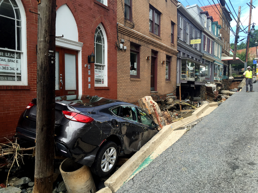 Workers gather by the sidewalk of Main Street that caved in after Saturday night's flooding in Ellicott City, Md., Sunday, July 31, 2016. Historic, low-lying Ellicott City, Maryland, was ravaged by floodwaters Saturday night, killing a few people and causing devastating damage to homes and businesses, officials said. (Kevin Rector/The Baltimore Sun via AP)