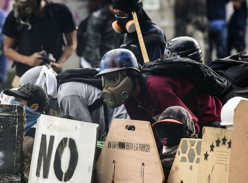 Anti-government activists clash with riot police during a protest in Caracas on July 28, 2017. Protesters took over streets in Caracas on Friday in a show of defiance to President Nicolas Maduro, as the crisis gripping Venezuela turned deadlier ahead of a controversial weekend election that has earned international scorn.  / AFP PHOTO / RONALDO SCHEMIDT